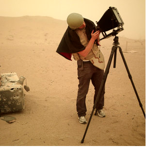 Richard Mosse, wearing helmet and bulletproof vest while using a large format camera in Iraq. The camera is similar to the one he would use later in the Congo.
